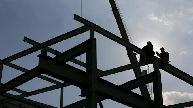 Men work on constructing a metal structure at a factory at the Keihin industrial zone in Kawasaki, south of Tokyo