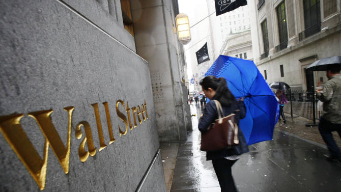 FILE - In this Aug. 25, 2010 file photo, a woman arrives for work on Wall Street on a rainy day in New York. U.S. stock futures headed higher Thursday, June 5, 2014, after the European Central Bank took new steps to boost the region's sluggish economy. The euro weakened against the dollar and U.S. government bond prices dipped. (AP Photo/Mark Lennihan, File)