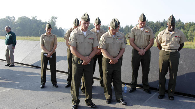 U.S. military personnel bow their heads as they observe a moment of silence to mark the exact time when the first hijacked airplane crashed into the World Trade Center on Sept. 11, 2001, as they stand at Phase 1 of the permanent Flight 93 National Memorial, near the crash site of Flight 93 in Shanksville, Pa., Sunday, Sept. 11, 2011.  (AP Photo/Amy Sancetta)
