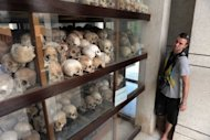 "A tourist looks at skulls displayed at the Choeung Ek killing fields memorial in Phnom Penh. Amnesty International has warned that a refusal by Cambodia's UN-backed court to appoint a defence lawyer in a politically sensitive new Khmer Rouge case has ""severely compromised"" the suspect's rights"