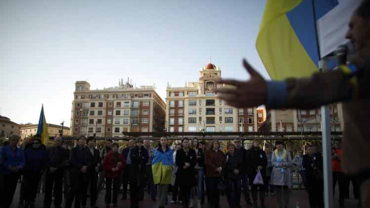 Ukrainians living in Malaga stand while a compatriot talks to them during a protest against Russian President Vladimir Putin and in favor of unity and democratic freedom in Ukraine, in downtown Malaga