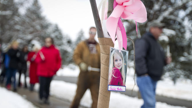 Visitors pass by a tree bearing the photo of Emilie Parker during the community dedication of a grove of trees at the Salt Lake City cemetery in remembrance of victims of the Newtown, Conn. shootings, Thursday, Dec. 27, 2012. Parker's parents Robbie and Alissa Parker originally hail from Ogden, Utah before they moved to Newtown. (AP Photo/The Deseret News, Ben Brewer)  SALT LAKE TRIBUNE OUT; PROVO DAILY HERALD OUT; MAGS OUT; MANDATORY CREDIT