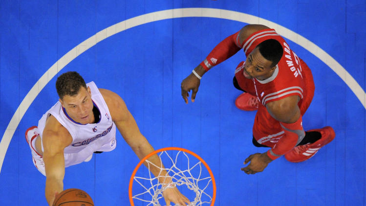 Los Angeles Clippers forward Blake Griffin, left, puts up a shot as Houston Rockets center Dwight Howard looks on during the first half of an NBA basketball game, Wednesday, Feb. 26, 2014, in Los Angeles. (AP Photo/Mark J. Terrill)