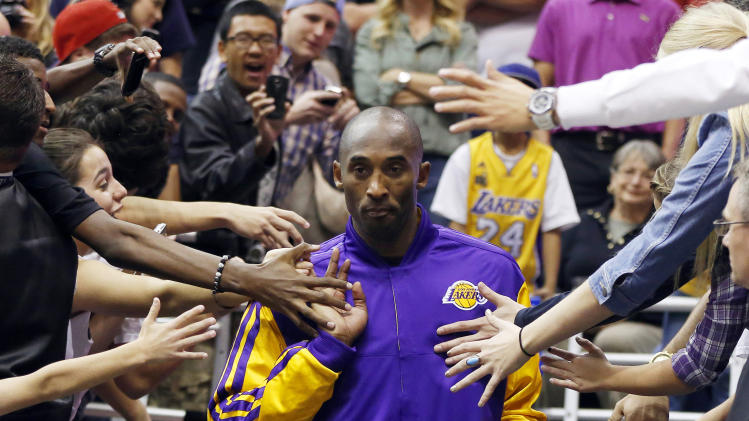 Los Angeles Lakers Kobe Bryant walks past fans before their NBA basketball game against the Utah Jazz in Salt Lake City