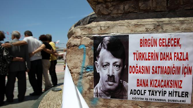 "A depiction of Turkish Prime Minister Recep Tayyip Erdogan portraying him as Nazi leader Adolf Hitler is pasted on the front of Mustafa Kemal Ataturk's statue, founder of Turkey, at the Taksim square in Istanbul on Thursday, June 6, 2013. The sign reads ''One day you are going to be married me because I haven't sold much Turkish nature.'' In the first days of the protests last week, Erdogan dismissed the demonstrators as ""capulcu"" - a Turkish word which translates as marauder, looter or plunderer. Protesters quickly turned the word to their advantage. They made it their own, Anglicizing it and turning it into a brand new verb, ""Capulling"" - which means protesting, resisting the tear gas and shouting anti-Erdogan slogans. (AP Photo/Thanassis Stavrakis)"