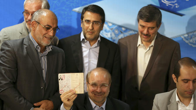 Tehran's mayor, Mohammad Bagher Qalibaf, a former Revolutionary Guard commander, shows his identification as he registers his candidacy for the upcoming presidential election, at the election headquarters of the interior ministry in Tehran, Iran, Saturday, May 11, 2013. Iranian election authorities say several new high-profile politicians including hardliners, reformists, and allies of outgoing President Mahmoud Ahmadinejad have registered for the June 14 presidential elections. The campaign is taking shape as open season on Ahmadinejad's legacy and his combative style that bolstered his stature among supporters but alarmed critics. Ahmadinejad is barred by law from seeking a third term due to term limits under Iran's constitution. (AP Photo/Ebrahim Noroozi)