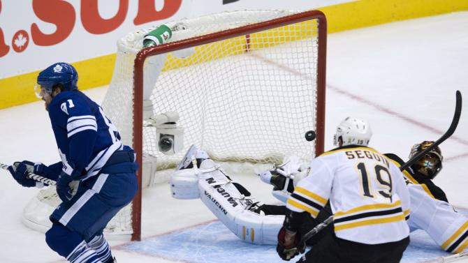 Toronto Maple Leafs forward Phil Kessel, left, scores past Boston Bruins goalie Tuuka Rask, right, as Bruins forward Tyler Seguin back centre, looks on during third period NHL hockey playoff action in Toronto on Sunday, May 12, 2013. (AP Photo/The Canadian Press, Nathan Denette)