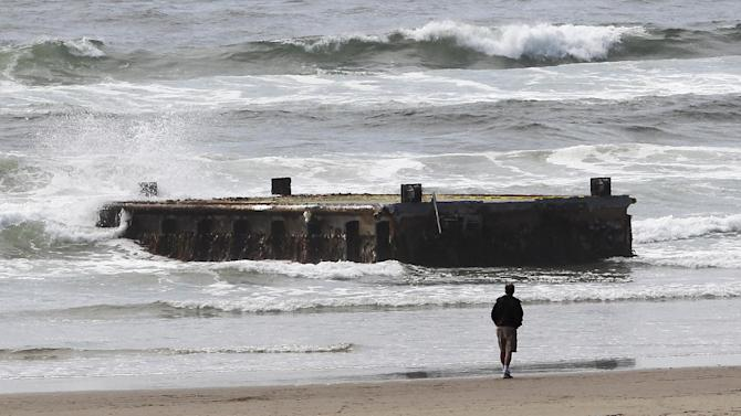 FILE - In this June 6, 2012, file photo, a man looks at the tsunami dock that washed ashore on Agate Beach in Newport, Ore.   A decision by a federal agency means Oregon may have to eat $350,000 it has spent on tsunami cleanup, including thousands to destroy and remove a 200-ton dock. (AP Photo/Rick Bowmer, File)