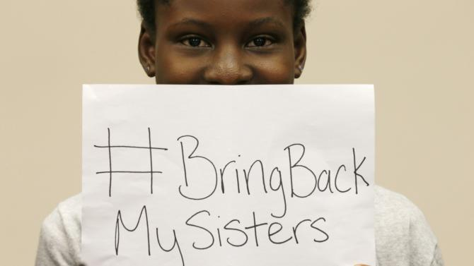 Nigerian teenager Deborah Peters, the sole survivor of a Boko Haram attack on her family in 2011, holds up a sign referring to the kidnapped Chibok secondary schoolgirls, while speaking to reporters on Capitol Hill in Washington