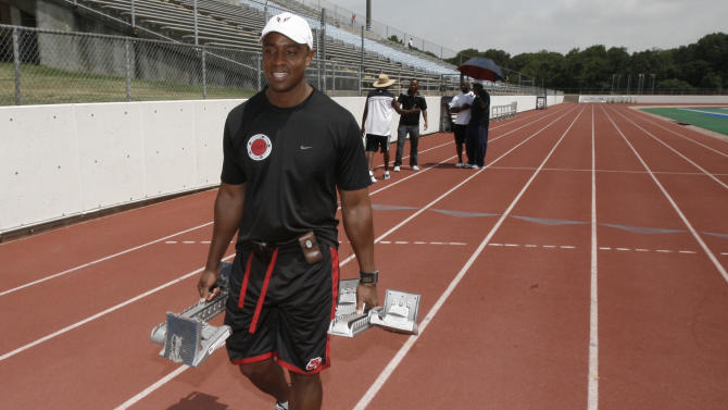 FILE - In this July 15, 2008, file photo, track coach Jon Drummond carries starters blocks to set up for a workout in Arlington, Texas. Drummond received an eight-year doping ban after arbitrators found he possessed, trafficked, administered and assisted in the use and cover-up of banned substances. The U.S. Anti-Doping Agency announced the ban Wednesday, Dec. 17, 2104. (AP Photo/LM Otero, File)