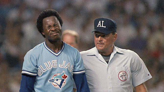 FILE - In this Aug. 11, 1988, file photo, Toronto Blue Jays' Tony Fernandez, left, reacts after he was hit on the head by a pitch by New York Yankees' Dave Eiland as umpire Don Denkinger stands nearby at Yankee Stadium in New York. Denkinger made a controversial call during the 1985 World Series which helped the Kansas City Royals eventually win the series. (AP Photo/Ray Stubblebine, File)