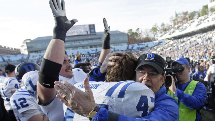 Duke coach David Cutcliffe hugs David Helton (47) following Duke's 27-25 win over North Carolina in an NCAA college football game in Chapel Hill, N.C., Saturday, Nov. 30, 2013. (AP Photo/Gerry Broome)