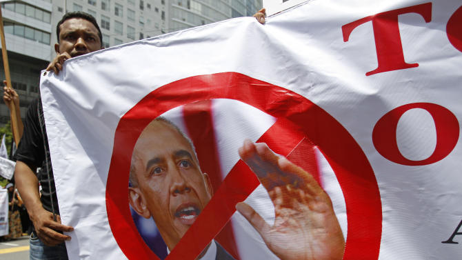 A Muslim protester holds a banner featuring a photo of U.S. President Barack Obama during a protest against the visit of Obama or Secretary of State John Kerry, scheduled for Oct. 11, outside the U.S. Embassy in Kuala Lumpur, Malaysia, Friday, Oct. 4, 2013. Obama is canceling a trip to Asia to stay in Washington and push for an elusive funding bill to get the nation's business back up and running. (AP Photo/Lai Seng Sin)