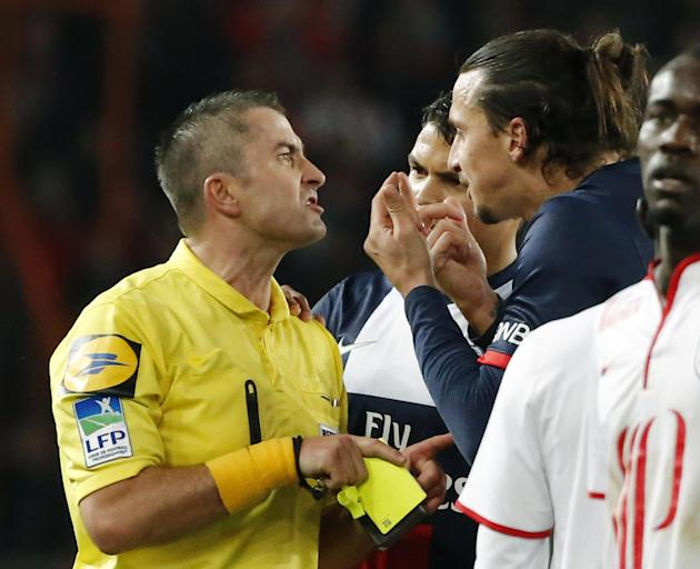 Referee Fredy Gautrel, left, argues with Paris-Saint-Germain's Zlatan Ibrahimovic of Sweden, right, after he was booked during a French league one soccer match between Paris-Saint-Germain and Lill
