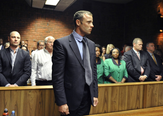 FILE - In this Feb. 19, 2013 file photo, olympian Oscar Pistorius stands following his bail hearing in Pretoria, South Africa. A judge in South Africa says Pistorius, who is charged with murdering his girlfriend, can leave South Africa to compete in international competition, with conditions. (AP Photo/File)
