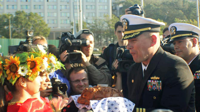 In this Sept. 20, 2012 photo made available by the U.S. Navy, Cmdr. Joseph R. Darlak, right foreground, commanding officer of the guided missile frigate USS Vandegrift, takes a bite of a traditional offering of bread and salt after arriving in Vladivostok for a port visit during operations in the Western Pacific. Cmdr. Darlak was relieved of command Friday, Nov. 2, 2012, in San Diego, after an investigation for demonstrating poor leadership and failing to ensure proper officer conduct during the three-day September stop. Executive officer Lt. Cmdr. Ivan A. Jimenez and the ship's chief engineer and operations officer were also relieved. The Navy cited use of alcohol and not adhering to behavior policies. (AP Photo/U.S. Navy Photo by Lt. J.G. Ryan P. Mutha)