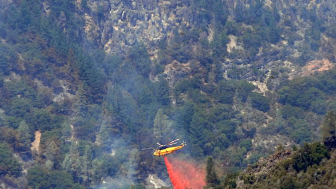 A helicopter drops fire retardant on the Ponderosa Fire deep in Battle Creek Canyon on Thursday, Aug. 23, 2012 west of Mineral, Calif.  The Ponderosa Fire is 57 percent contained, with full containment expected early next week. (AP Photo/Jeff Barnard)