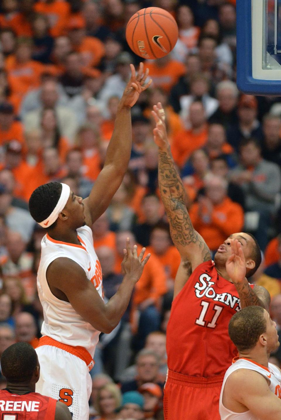Syracuse's C. J. Fair, left, shoots over St. John's D'Angelo Harrison during the first half of an NCAA college basketball game in Syracuse, N.Y., Sunday, Feb. 10, 2013. (AP Photo/Kevin Rivoli)