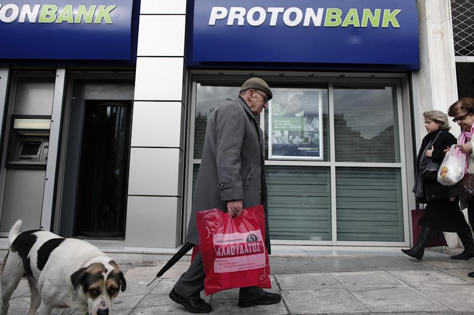 Pedestrians walk in front of a branch of Proton bank in central Athens, Friday, Dec. 14, 2012. Prominent Greek businessman Lavrentis Lavrentiadis was arrested Thursday Dec. 13 over his alleged involvement in a scandal involving the Proton Bank, in which he was the major shareholder. (AP Photo/Petros Giannakouris)