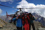 Rescuers assist a foreigner who was injured following an avalance at the Mount Manaslu base camp in Gorkha District, in this photograph released by Nepalese helicopter aviation service Simrik Air. The avalanche killed at least nine climbers trying to scale one of the world's most deadly peaks, according to officials
