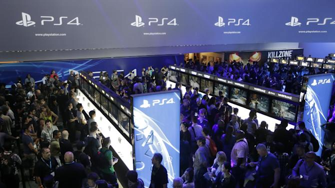 """FILE - In this June 11, 2013 file photo, show attendees play video games on the new Sony PlayStation 4 at the Sony booth during the Electronic Entertainment Expo, in Los Angeles. Twitch is coming to the PlayStation 4; the popular streaming video service that allows gamers to broadcast footage online was previously announced as a feature for Microsoft's Xbox One. Sony said Tuesday, Aug. 20, 2013, the service would also be available on the PS4, which adds a """"Share"""" button to its new controller. (AP Photo/Jae C. Hong, File)"""