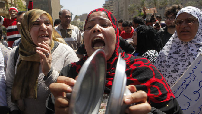 An Egyptian woman bangs cooking pot lids together and shouts anti-Muslim Brotherhood slogans during a protest in Tahrir Square, the focal point of Egyptian uprising, to support judicial independence in Cairo, Egypt, Friday, April 26, 2013. Egypt's Islamist-led parliament on Wednesday pushed ahead with a law that could force into retirement many of the nation's most senior judges, despite an uproar by the judiciary over fears the president's allies want to control the courts.(AP Photo/Amr Nabil)