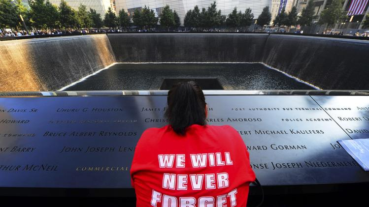 A woman pauses for reflection at the 9/11 Memorial during ceremonies marking the 12th anniversary of the 9/11 attacks on the World Trade Center in New York