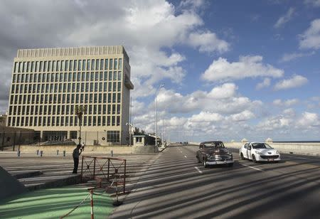 Cars drive past the U.S. Interests Section, in Havana