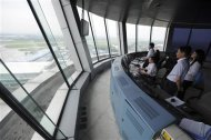 Employees look out from a control tower of Hefei Luogang Airport in Hefei, Anhui province May 29, 2013. REUTERS/Stringer