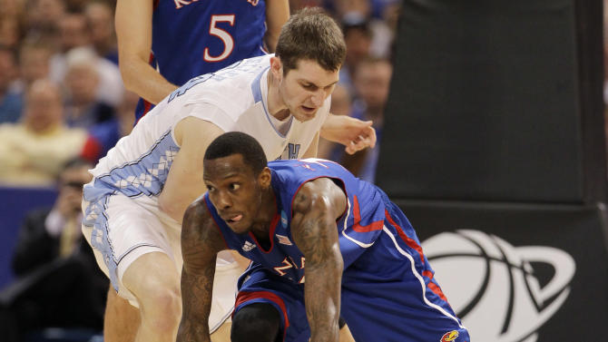 Kansas guard Tyshawn Taylor chases a loose ball against North Carolina forward Tyler Zeller, left, during the first half of the NCAA men's college basketball tournament Midwest Regional final Sunday, March 25, 2012, in St. Louis. (AP Photo/Jeff Roberson)