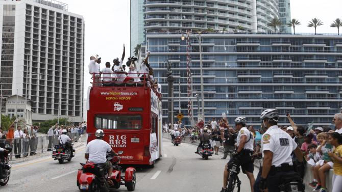 Miami Heat's LeBron James, center, waves from a doubledecker bus during a parade through downtown in celebration of winning the NBA Finals basketball championship against the Oklahoma City Thunder, Monday, June 25, 2012, in Miami. (AP Photo/Lynne Sladky)