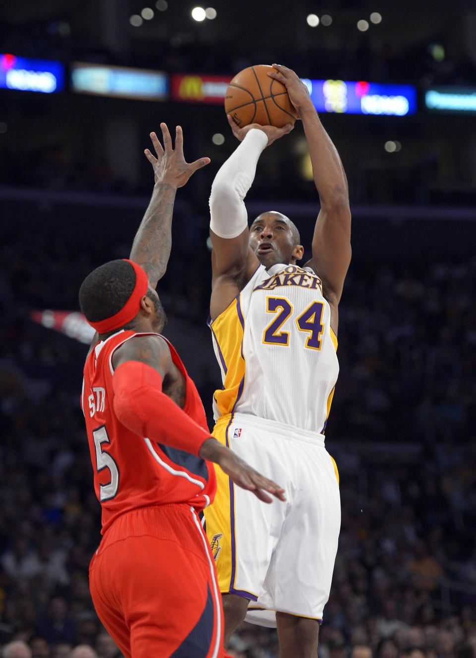Los Angeles Lakers guard Kobe Bryant, right, puts up a shot as Atlanta Hawks forward Josh Smith defends during the first half of their NBA basketball game, Sunday, March 3, 2013, in Los Angeles. (AP Photo/Mark J. Terrill)