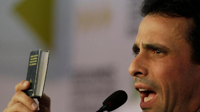 "Opposition leader Henrique Capriles holds up a copy of the Venezuelan Constitution as he speaks during a news conference in Caracas, Venezuela, Wednesday, Jan. 9, 2013. Capriles condemned the Supreme Court's endorsement of delaying the inauguration. ""Institutions should not respond to the interests of a government,"" he said. (AP Photo/Fernando Llano)"
