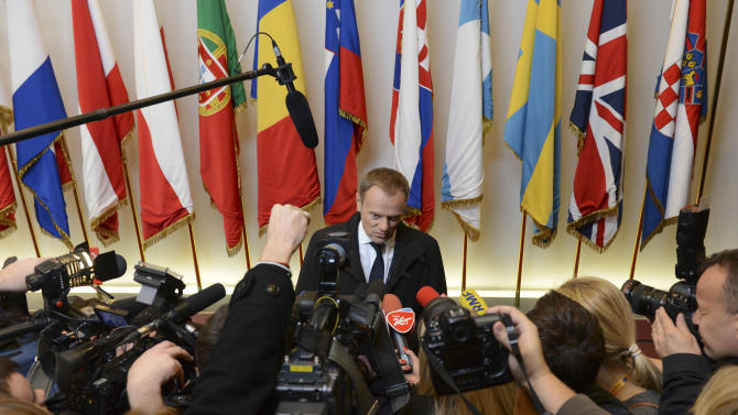 Poland's Prime Minister Donald Tusk, center, speaks with the media as he arrives for an EU summit  in Brussels on Thursday, Nov. 22, 2012. EU leaders begin what is expected to be a marathon summit on the budget for the years 2014-2020. The meeting could last through Saturday and break up with no result and lots of finger-pointing. (AP Photo/Geert Vanden Wijngaert)