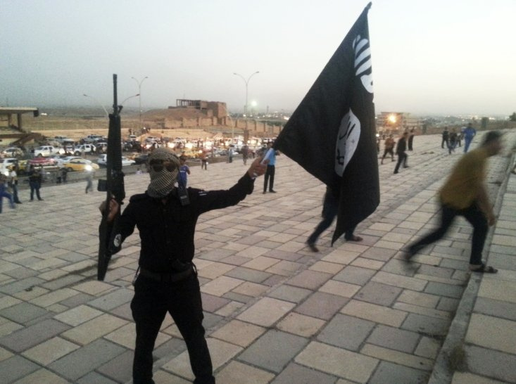 CLICK IMAGE for slideshow: A fighter of the Islamic State of Iraq and the Levant (ISIL) holds an ISIL flag and a weapon on a street in the city of Mos...