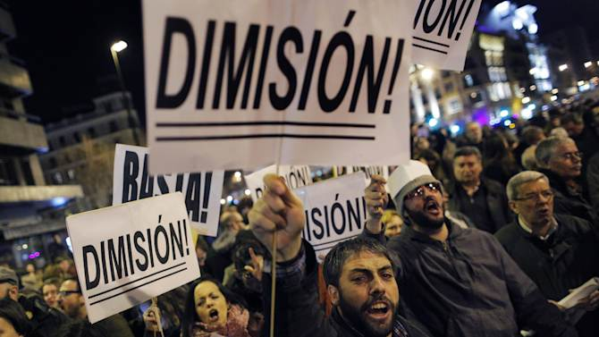 """Protestors hold banners reading, 'resign' 'this is enough' during a demonstration against corruption, in Madrid, Spain, Thursday, Jan. 31, 2013. Spain's governing Popular Party insists its financial accounts are totally legal and denies a newspaper report of regular under-the-table payments to leading members, including current Prime Minister Mariano Rajoy. The scandal first broke when after the National Court reported that former party treasurer Luis Barcenas amassed an unexplained euro 22 million ($30 million) in a Swiss bank account several years ago. In a statement Thursday Jan. 31, 2013, the party denied the existence of """"hidden accounts"""" or """"the systematic payment to certain people of money other than their monthly wages. (AP Photo/Andres Kudacki)"""