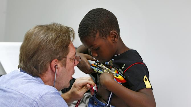 "Migrant Kuapana from Congo receives a medical check-up from doctor Mathias Wendeborn, at a refugee camp set-up in the former German army base ""Bayernkaserne"" in Munich"