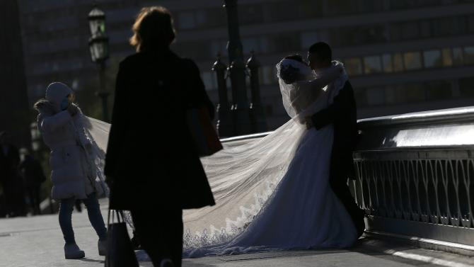 A couple poses for a wedding photographer in central London