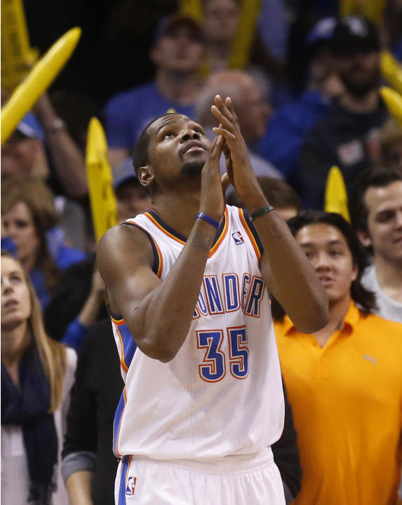 Oklahoma City Thunder forward Kevin Durant (35) claps his hands as he looks up at the scoreboard as the game clock winds down in the fourth quarter of an NBA basketball game against the Sacramento Kin