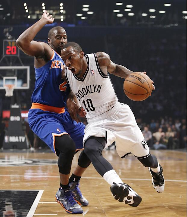 Brooklyn Nets guard Tyshawn Taylor (10)  drives past New York Knicks guard Raymond Felton (2) in the first half of their NBA basketball game at the Barclays Center, Thursday, Dec. 5, 2013, in New York