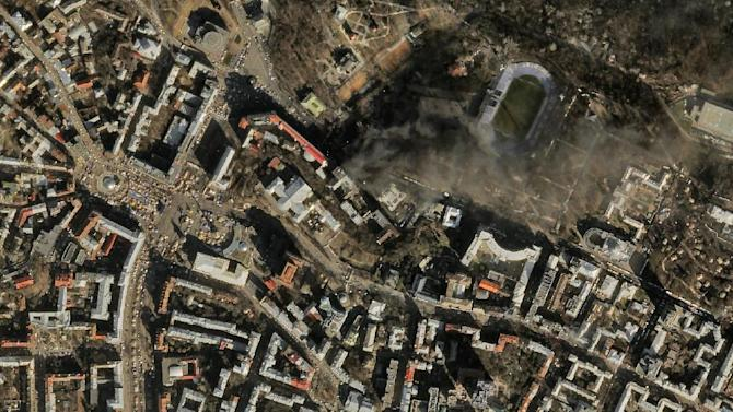 In this satellite image provided by Skybox Imaging and taken by SkySat-1 on Tuesday, Feb. 18, 2014 at 11:10 a.m. local time, smoke rises from the site of anti-government protests, upper center, in Kiev, Ukraine. Thousands of riot police armed with stun grenades and water cannons attacked the sprawling protest camp in the center of Kiev on Tuesday, following a day of street battles that left 18 people dead and hundreds injured. (AP Photo/Skybox Imaging) MANDATORY CREDIT