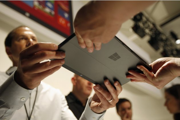 A Microsoft representative hands the new Surface to a member of the press as it is unveiled by Microsoft in Los Angeles