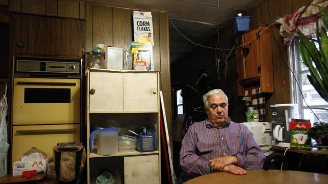 In this Sept. 15, 2011 photo, Bill Ricker, 74, sits at the kitchen table of his trailer home, in Hartford, Maine. Ricker, who has two college degrees, was injured in the late 1980s and hasn't worked since. Now he receives food stamps and heating fuel assistance and gets donations from a local food pantry. (AP Photo/Robert F. Bukaty)