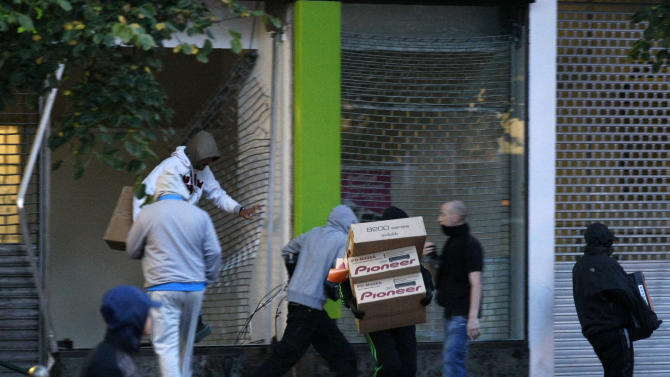 Looters take electrical goods after breaking into a store during the second night of civil disturbances in central Birmingham, England, Tuesday, Aug. 9, 2011. Britain began flooding London's streets with 16,000 police officers Tuesday, nearly tripling their presence as the nation feared its worst rioting in a generation would stretch into a fourth night. The violence has turned buildings into burnt out carcasses, triggered massive looting and spread to other U.K. cities. (AP Photo/Tim Hales)