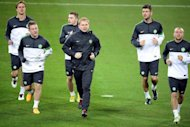 Celtic manager Neil Lennon (C) leads players in a warm up during a training session, March 5, 2013. Captain Scott Brown says the Celtic players are all desperate for Lennon to stay at the Glasgow giants following speculation linking him to the vacant position at Everton
