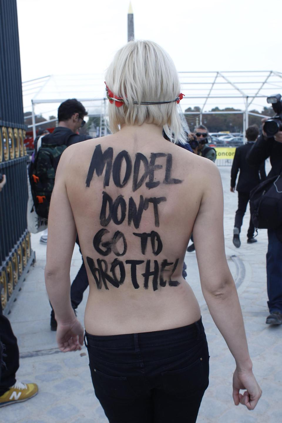 An activist of Femen, a feminist Ukrainian protest group, leaves the Tuileries Gardens after two of them were removed by security staff while disturbing the presentation of Nina Ricci's ready-to-wear Spring/Summer 2014 fashion collection Thursday, Sept. 26, 2013 in Paris. (AP Photo/Thibault Camus)