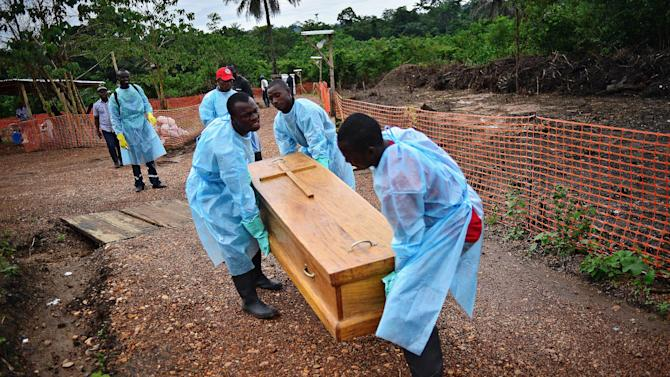 Sierra Leonese government burial team members wearing protective clothing carry the coffin of an Ebola victim on August 14, 2014 in Kailahun