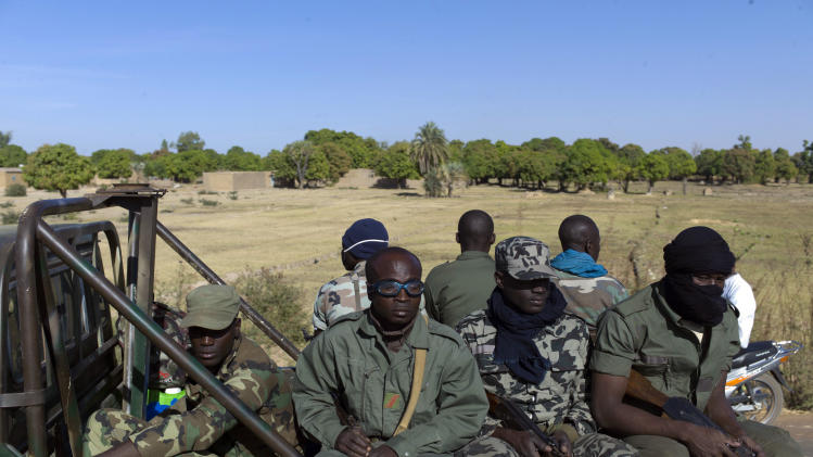 Malian soldiers are seen on their way to Niono, Mali, some 270 kms (180 miles) north of Bamako, Friday, Jan. 18, 2013.  French troops encircled a key Malian town on Friday to stop radical Islamists from striking closer to the capital, a French official said. The move to surround Diabaly came as French and Malian authorities said they had retaken Konna, the central city whose capture prompted the French military intervention last week. (AP Photo/Thibault Camus)