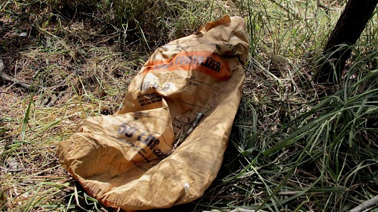 An empty fertilizer bag is left behind at a two-acre pot farm is hidden in the brush in Raymondville, Texas on Thursday, Aug. 21, 2014. Authorities found the operation, which is rare so close to the border, while attempting to capture immigrants who fled into it on Aug. 13, 2014. (AP Photo/Christopher Sherman)