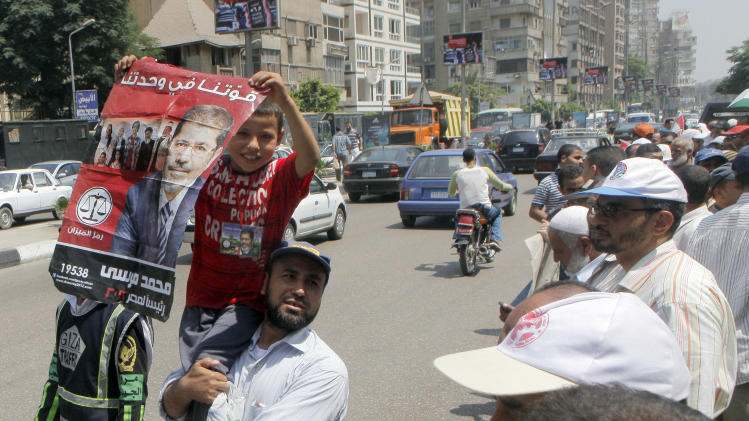"An Egyptian supporter of President Mohammed Morsi carries his son holding a poster in Arabic that reads, ""our strength in our unity,"" during a rally in front of Egypt's state council in Cairo, Egypt, Tuesday, July 10, 2012. Egypt's Islamist-dominated parliament convened Tuesday in defiance of a ruling by the country's highest court and swiftly voted to seek a legal opinion on the decision that invalidated the chamber over apparent election irregularities. (AP Photo/Amr Nabil)"
